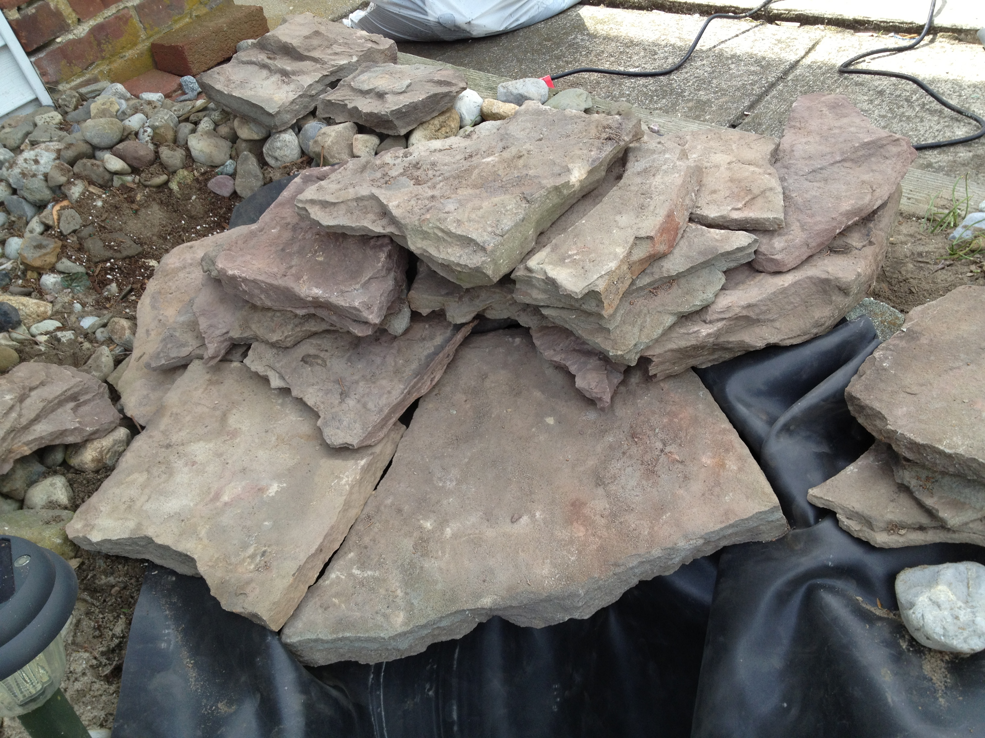 How to build a garden waterfall pond a girl 39 s guide to diy for Garden pond edging stones